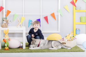 Happy Easter! Happy baby boy playing with dog on Easter day. Easter decoration